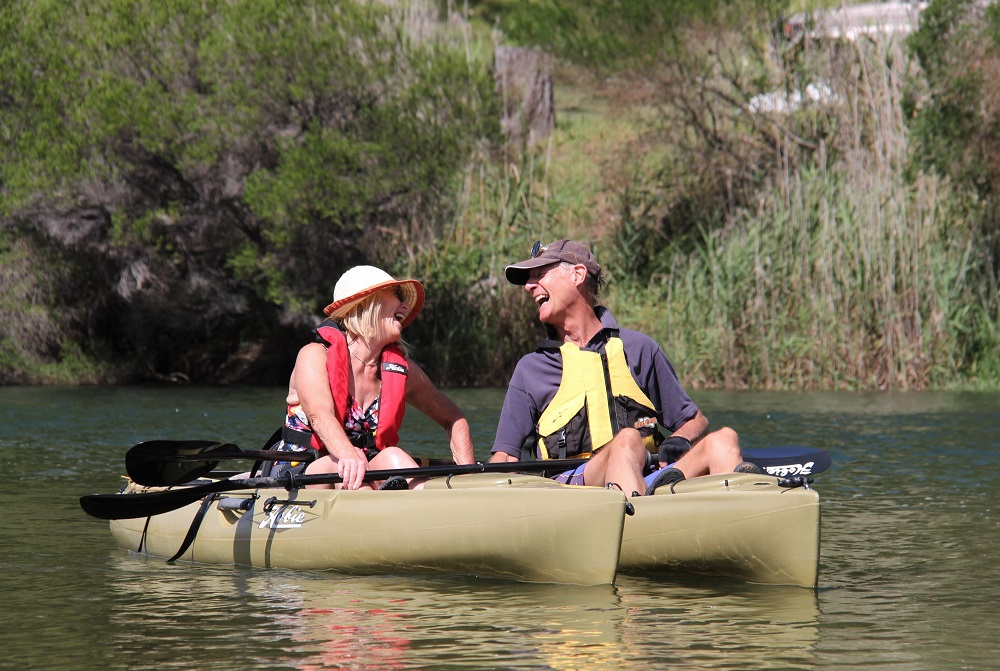 Couple smiling on kayaks